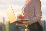 Woman in the office suit with a laptop on the balcony of the office building on the New York city background.