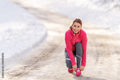 canvas print picture Woman tying shoelace while crouching on the trail at winter. Outdoor fitness concept.