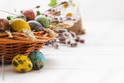 Easter eggs in a basket on a white wooden background - 261960284