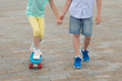 the boy holds the girl's hand, teach skating on a sports Board, legs close-up, on the background of stone blocks