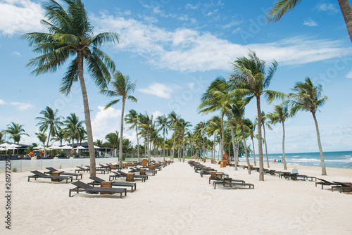 Beach chairs on the white sand beach with cloudy blue sky and sun. Vacation concept - 261972292