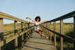 Joyful woman dancing and having fun on vacation. Spring or summer outdoor relaxing leisure. Afro hair young black female.