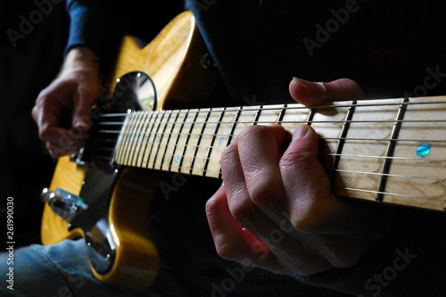 Guitarist playing a natural wood electric guitar in moody light with focus on fingers of fret hand on maple fingerboard. - 261990030