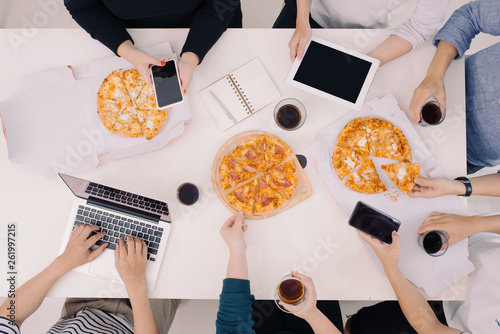 canvas print picture Business team is eating pizza at work while working