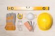Yellow hardhat, gloves and hammer isolated