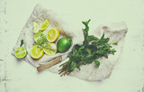 Fresh lemons, lime and herbs for making a lemonade or detox drink. Healthy and natural food ingredients. Flat lay. Copy space