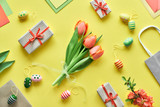 Easter flat lay on yellow paper. Bunch of tulips, gift boxes, decorative eggs and paper bags, geometric diagonal arrangement.