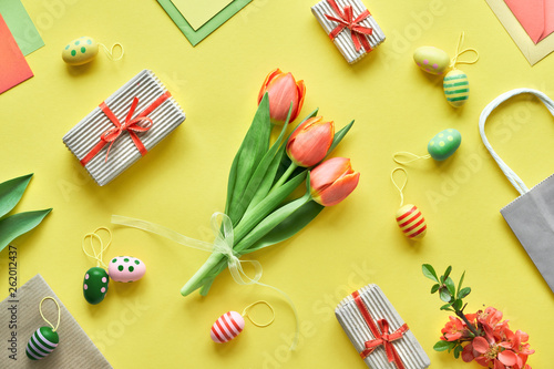 Easter flat lay on yellow paper. Bunch of tulips, gift boxes, decorative eggs and paper bags, geometric diagonal arrangement. - 262012437