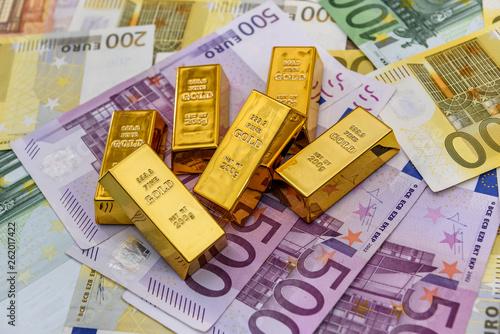 Gold bullions at euro banknotes background closeup