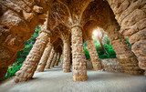 Barcelona, Spain. Park Guell. Antonio Gaudi Art Architecture. Stone pillars with archs at sunset among green trees and plants. Famous touristic destination landmark for walking tours.