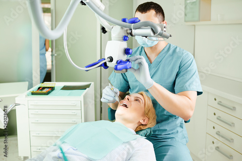 Dentist man with a microscope checks the teeth of a girl patient - 262028678