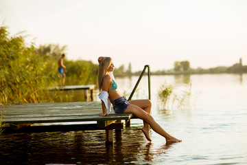 Young woman sitting on the pier on the lake © Boggy