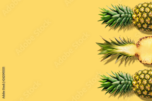 Fresh pineapples on yellow background. Creative suumer concept. - 262045031