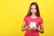 Young girl holding pink piggybank on yellow background