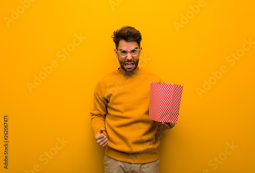 Young man holding popcorns screaming very angry and aggressive