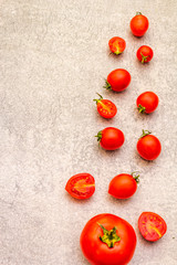 Fresh organic tomatoes. Food cooking stone background. Healthy vegetarian (vegan) eating concept, copy space, close up, top view, flat lay.