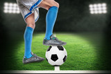 Spotlight on Soccer Player Standing Over Football in Outdoor Stadium With Copy Space