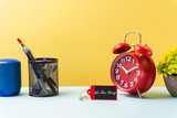 conceptual images. written text  on the mini wooden board woth alarm clock, vase and stationery against yellow background