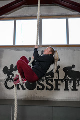 young girl climbs the rope in the crossfit room