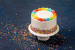 White Birthday cake with rainbow icing and colorful Sprinkles over a dark blue background.