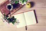 Still-life with open blank notebook, old book and apple