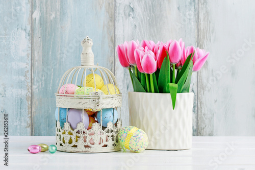 Easter eggs inside a vintage bird cage and bouquet of pink tulips in ceramic vase.