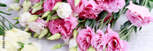 Pink and yellow eustoma (lisianthus) flowers on table.