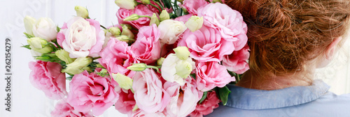 Woman florist carrying a big bunch of pink eustoma flowers.