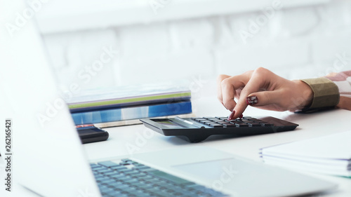 Close up of woman hands with calculator counting and taking notes to laptop. Job of an accountant freelancer for the calculation of tax deductions. © cameravit