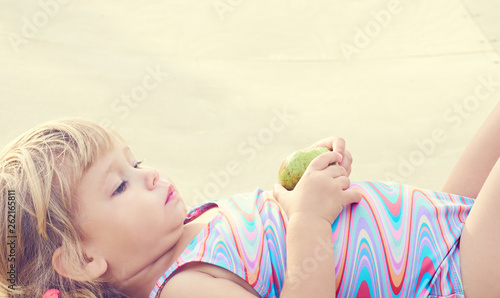 canvas print picture Cute adorable toddler girl eating fresh pear lying on the beach.