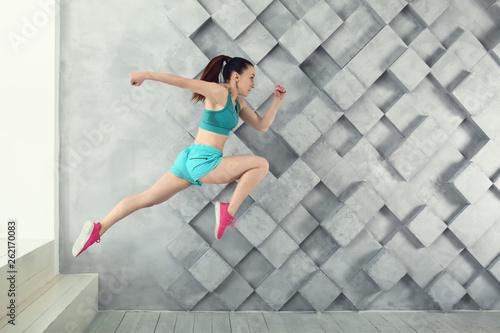 Leinwandbild Motiv Sporty running woman against grey wall