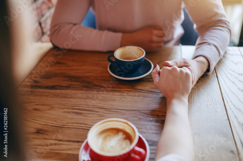 Young couple in love sitting in cafeteria and holding hands. On desk cups with coffee. © dusanpetkovic1