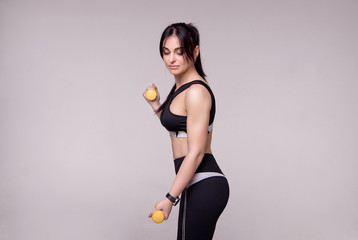 Portrait of a sporty young European fitness woman doing workouts with dumbbells isolated on gray background © Viktoria