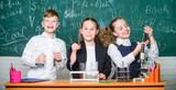 Group school pupils study chemical liquids. Girls and boy student conduct school experiment with liquids. Check result. School chemistry lesson. Test tubes with colorful substances. School laboratory