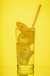 Leinwandbild Motiv Full glass of fresh cool transparent water with lemon on yellow background