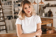 Portrait of beautiful blond woman smiling and rejoicing while standing in stylish wooden kitchen at home