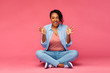 emotions, expressions and people concept - happy excited african american woman sitting on floor over pink background