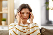 people , health and stress concept - unhappy woman suffering from head ache at home - 262210827