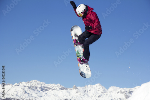 fototapeta na ścianę Snowboarder jumping through air with blue sky in background