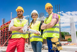 Portrait of three confident and reliable young employees at construction site