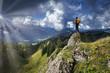 canvas print picture - Mann auf Berggipfel mit Sonnenstrahlen