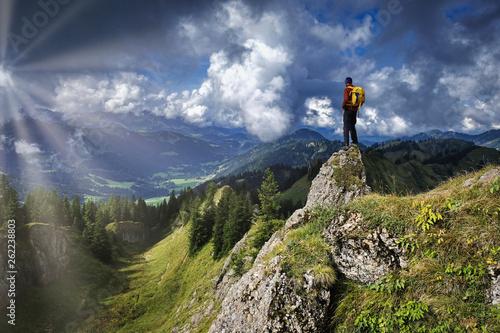 canvas print picture Mann auf Berggipfel mit Sonnenstrahlen
