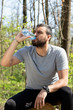 canvas print picture - Portrait of handsome young man athlete drinking water in forest