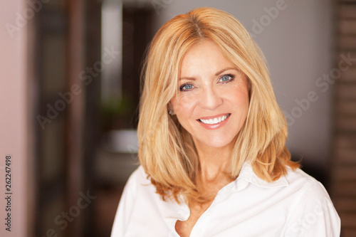 canvas print picture Mature woman smiling at the camera. She relaxing at home