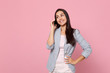 Smiling young woman in striped jacket talking on mobile phone, conducting pleasant conversation isolated on pink pastel wall background. People sincere emotions, lifestyle concept. Mock up copy space.