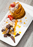 Stack of sweet pancakes with  fruit, honey, chocolate and whipped cream