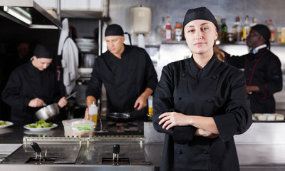 Confident female chef with a team of cooks in restaurant kitchen
