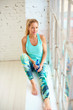 Beautiful blond woman relaxing after workout and drinking water
