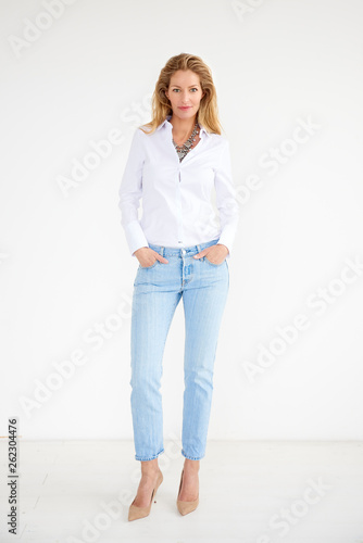 canvas print picture Full length shot of attractive middle aged woman wearing casual clothes while standing at isolated background