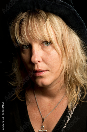 canvas print picture Portrait of a blond woman with black hat. The close up is very personal. Looking at the camera. She is vulnerable.